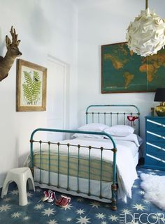 In this Moroccon home, the daughter's room includes a vintage iron bed that came from a Marrakech flea market. The map is vintage, the light fixture is by Claire Norcross for Luminosity, and the print is by Roger Sandes.