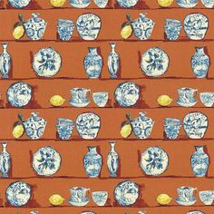 A blue and white plate pattern on an orange background also featuring lemons. This fabric is a medium weight and is suitable for upholstery, window treatments, bedding, and pillows.