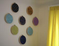 Amostras de tricô esticadas em bastidores de bordado e penduradas na parede