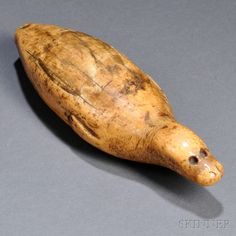 Lot 108   Inuit Carved Walrus Tusk Seal Figure, 19th century, the end of the figure pierced, lg. 7 1/4 in.   Estimate $800-1,200     The eye sockets are vacant.