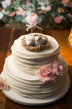 Bolo de Casamento romântico, com topo de bolo de passarinhos no ninho, e detalhes em rosa. Bolo de casamento ao ar livre.