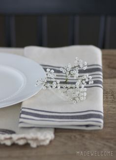 Host a get together using cloth napkins, fresh berries with chocolate cake, silver, flowers on the napkins. #clothnapkins #farmtable #dessert #berries #babysbreath #flowers