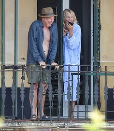 Meanwhile... 69-year-old Neil kept his cool in a plain blue shirt and grey knee-length sho...