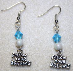 "Handcrafted by Teal Palmetto, LLC. Great advice!  Silver-tone pewter charms that say ""Follow Your Dreams"" are joined by white and blue accent beads.  This pair has silver fish hook ear wires. Price: $14."
