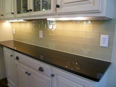 Light colored cabinets with dark brown countertop, cream colored subway tile, dark bronze hardware