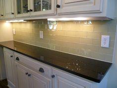 Light colored cabinets with dark brown countertop, cream colored subway tile, dark bronze hardware