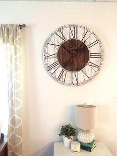 Looking for just the right rustic touch to add to your living room? This handcrafted farmhouse style clock will add a country feel to whatever room you hang it in. Its made of re-purposed pallet wood with hand painted numbers. It is white-washed painted with black roman numerals.  Clock comes with hardware attached to the back ready to hang on your wall! Clock motor takes one AA battery which is not included. All clocks can be customized according to your desires--whether it be a different…