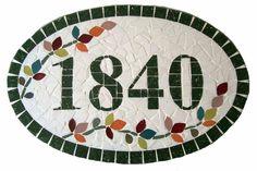 Numero residencial em mosaico, tamanho oval médio (38x25). Cliente pode escolher cor da borda e do número. O mosaico é realizado em cima de um piso e deverá ser fixado na parede com argamassa.