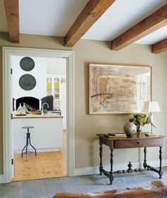Bluestone paves the main foyer of Edwina Hunt's home in Dutchess County, New York, which features a mixed-media work by María Noël, a horn-and-silver lamp designed by Hunt, and a 19th-century French table from a Paris flea market.