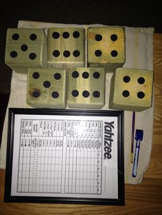 Lawn Yahtzee.  I made the dice from 4x4 posts cut square and rounded the edges slightly before painting on the dots. I put on a clear top coat to protect the wood from the elements.  I enlarged the score sheet and placed it in a dollar store frame. We use a dry erase marker to keep score. It cleans easily.