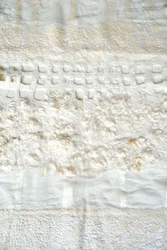 Wandkleed van extra fijne merino wl en zijde, gecombineerd met ruwe schapenwol en chiffonzijde. Het is ambachtelijk gevilt met verschillende technieken. Kleur; Tinten wit. Maat: 70 x 120 cm