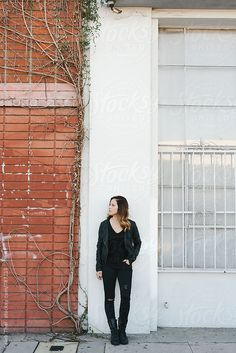 A girl dressed in black against an outside white wall