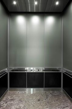LEVELe-105 Elevator Interior with upper panels in ViviChrome Chromis glass with custom color interlayer and Opalex finish; lower panels in Fused Graphite with Sandstone finish; and Rectangular handrails in Polished Stainless Steel at Mission City Corporate Center, San Diego, California