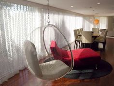 A suspended bubble chair hangs next to a plush red velvet chaise set on a circular gray fur rug in this unique seating area.