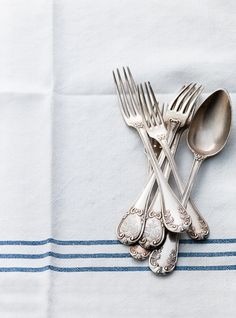Vintage flatware on linen.  Dry it completely before storing an anti-tarnish flatware rolls like the ones from Sherwood Silver Bags.