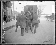 Police putting a woman into the back of a police wagon during a garment workers strike, 1910. DN-0056132.