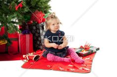 image of a cute baby girl with christmas tree and gift box in background. - Image of a cute baby girl with Christmas tree and gift box in background. Model: Hannah Phillips
