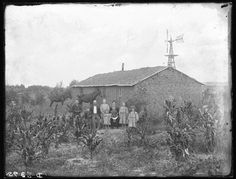Couple and seven children in front of a sod house, Custer County, Nebraska.
