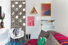 Quarto de TV tem piso de epoxi azul, parede com quadros e divisória de cobogó.