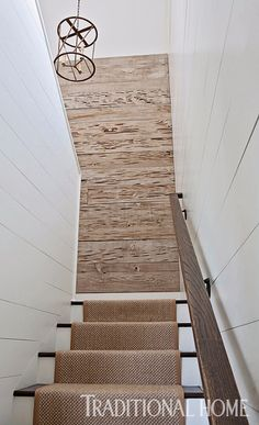 Pecky cypress and white wood-plank walls add interest to an ordinary stairwell. - Photo: Paige Rumore / Design: Rachel Halvorson