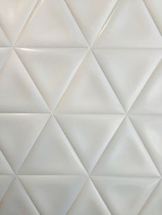 These Elvida triangular shaped white tiles from Vives do away with basic rectangular shaped tiles and add a bit of puffiness to each one making them appear more three dimensional.