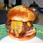 Bronco Burger.   5 fresh jalapeno peppers  4 pounds ground beef  salt & pepper to taste  1 egg  1/4 cup steak sauce  1/4 minced white onion  1 tsp tabasco sauce  1 pinch dried oregano  1 Tbs wotcestershire sauce  1 tsp garlic salt  1/4 cup crushed Fritos chips  8 large burger buns  8 slices pepperjack cheese