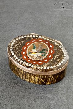 Presumably Dresden, 90 x 70 x 34 mm, 149 g, circa 1780  A rare rose gold-mounted hardstone snuff box in the manner of the Saxon gemstone snuff-boxes by Johann Christian Neuber (1736-1808), Dresden Case: oval agate box, hinged lid with carved pearl motif border; central oval medallion with inlaid red and white braided border with engraved lyre, book, scroll, quill and ink pot and laurel leafs in a small gold frame. The gold fittings on the edge of the lid are decorated with engraved foliate…