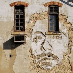 Street art : Closeup of a portrait carved on the facade of a house by Vhils under the CRONO Project in Portugal.