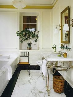 Late British colonial style is signaled by the high ceiling, cool white walls, classic marble, vintage sconces & ebonized faux-bamboo & rattan chair.