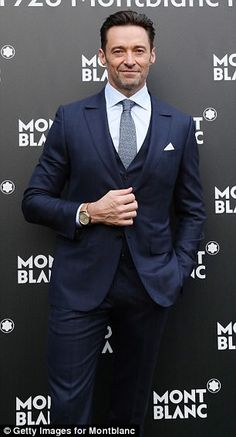 Suited and booted! The Wolverine star looked typically suave as he posed in a navy two-piece suit and matching tie
