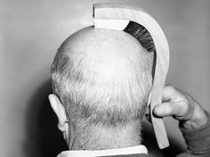 """Mr. Ted Spence, engineer of the Los Angeles Brush Manufacturing Corp., demonstrates the new """"Hairline Brush"""" in Los Angeles, Calif., Jan. 12, 1950. The brush is constructed to fit a bald head's contour, with bristles for brushing the side-burn area and a felt pad to gently massage the exposed scalp on the top."""