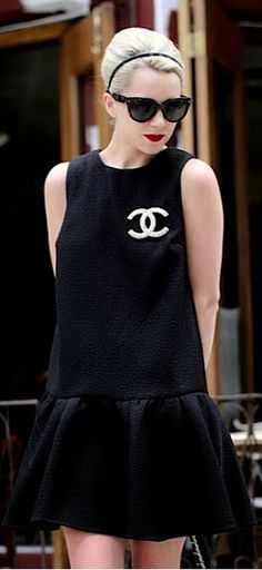Here is a modern day little black dress by Chanel. The silhouette is still extremely simple giving the dress an easy chicness. The only decoration on the gown is the timeless Chanel double-C logo as a brooch.