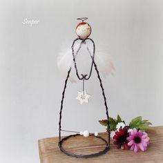 Andělka s hvězdičkou Drátovaná figurka - soška andělky z černého žíhaného drátu zdobená keramickou hlavičkou holčičky od Kronmon74. Soška je milou dekorací, nejen pro snílky :) Andělku zdobí bílá pírka, dřevěná hvězdička s flitry a bílé dřevěné korálky. Rozměry : výška cca 20 cm, průměr podstavce cca 8 cm. ...
