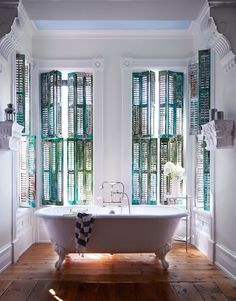 claw-foot tub surrounded by shutters painted in varying shades of green