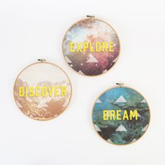 """This set of three 9"""" Hoop Art Wall Hangings is inspired by a quote from Mark Twain. Set Includes: • EXPLORE - with a galactic image • DREAM - with an underwater background, • DISCOVER - with a beautiful mountain landscape Material: Canvas, wood; Stretched in embroidery hoops (item is not embroidered) Size: 9"""" Diameter"""