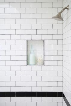 black stripe in basement bathroom shower. you could maintain the black and switch to a different tile for the cap on the wainscott around the entire bathroom.