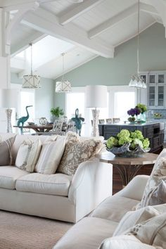 Sherwin Williams Sea Salt in a beach style living room with vaulted ceilings and white beams and neutral furnishings