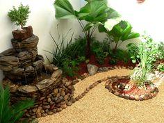jardin pequeño con fuente de agua, palmas, piedras y bonsai