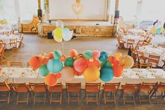 Barn wedding decoration using bright color paper lanterns. Paper lanterns are grouped in a cluster over the bride and groom table.
