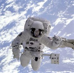 """Original caption: """"The pale blue Earth serves as a backdrop for astronaut Michael Gernhardt, who is attached to the Shuttle Endeavour's robot arm during a spacewalk on the STS-69 mission in 1995. Unlike earlier spacewalking astronauts, Gernhardt was able to use an electronic cuff checklist, a prototype developed for the assembly of the International Space Station."""""""