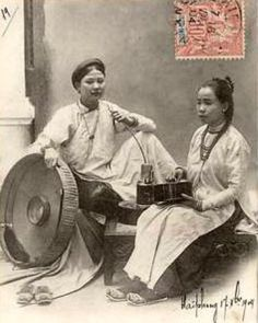 On a postcard dated 1904, two women wear áo ngũ thân, the form of the ao dai worn in the nineteenth and early twentieth centuries.