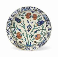 AN IZNIK POTTERY DISH   OTTOMAN TURKEY, CIRCA 1575   With sloping rim on short foot, the white interior painted in cobalt-blue, green and bole-red with a symmetrical design of tulip and peony sprays in a narrow stylised wave and rock border, the reverse painted with stylised paired blue tulips alternating with green flowerheads, one repair to border, two hair cracks  12¾in. (32.3cm.) diam.