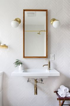 white tile bathroom with brass fixtures