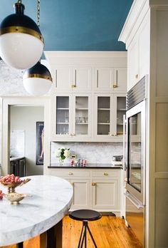 Bungalow Blue Interiors - Home Glass fronted cupboards, marble backsplash,  black marble countertop, white marble topped  centre table