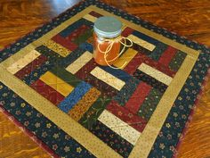 Handmade Quilted Wall Hanging/Table Topper in fabrics of dark red, blue, green, brown and beige by RubysQuiltShop on Etsy