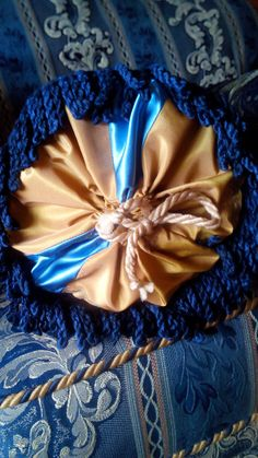 Victorian Style Bolster Cushion. Made out of a strong upholstery fabric in black and gold with a beautiful elephant print and decorated on the ends with a dark blue ribbon. The rosette is made out of blue satin and a gold colour mixed satin. and closes with a ribbon. The inside pillow is