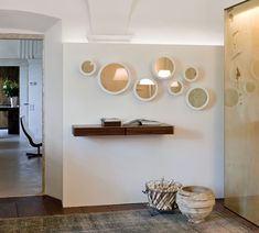Stars: diseño de Colzani para Porada. Espejos redondos con marco y soporte de metal a pared con percha para colgar prendas. Para su uso sueltos o en composición.