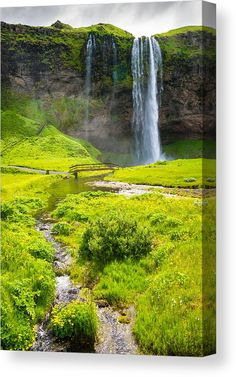 Waterfall in Iceland Canvas Print for sale. Seljalandsfoss and a lovely summer landscape, fresh green meadows and a small river. The image gets printed on one of our premium canvases and then stretched on a wooden frame, click through and check out your options. 30 days money back guarantee. Matthias Hauser - Art for your Home Decor and Interior Design.
