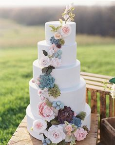How gorgeous! Tiered wedding cake with fresh flower cascade