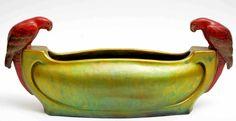 Zsolnay - Papagájos kínáló, 1919-1921 Porcelánfajansz, márványosan összefolyó opak és transzparens eozinmázak, plasztikusan ráillesztett díszítés, a vázatest savmaratott, Szélesség: 38 cm, M: 16 cm Jelzés: Pontozott körvonalban az öt templomtorony belső körívén Zsolnay Pécs, illetve alatta két sorban Made in Hungary feliratú márkajelzés, F: 8850
